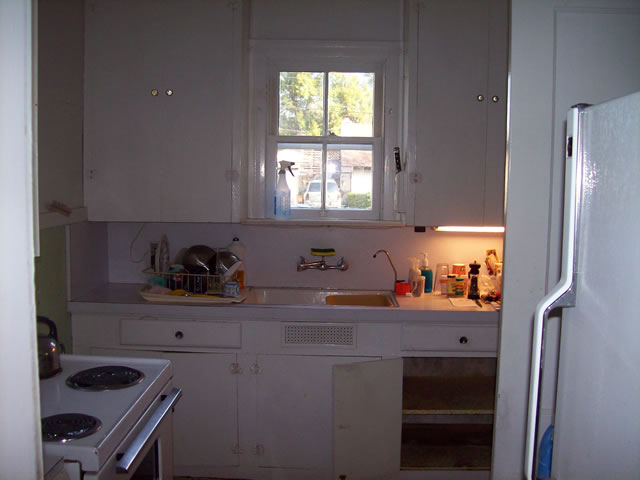Before photos of a kitchen built in the 1950s. We relocated sink, range, microwave. Replaced cabinets with granite counter tops. Reswung rear exterior door and converted interior swing door to a pocket door. Also installed ceramic tile,paint and electrical.